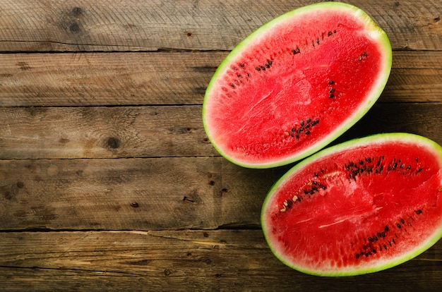 Geschmackvolle organische wassermelone geschnitten zur hälfte auf hölzernem