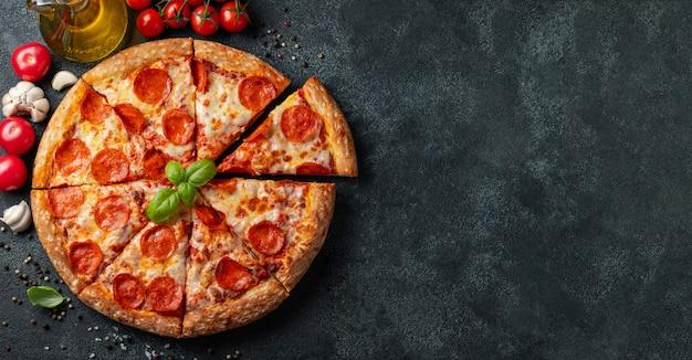 Geschmackvolle pepperonipizza auf einem schwarzen konkreten hintergrund.