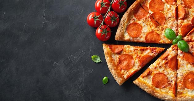 Geschmackvolle pepperonipizza auf schwarzem konkretem hintergrund