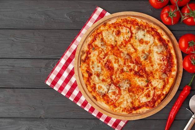 Geschmackvolle pizza auf draufsicht des schwarzen hölzernen hintergrundes
