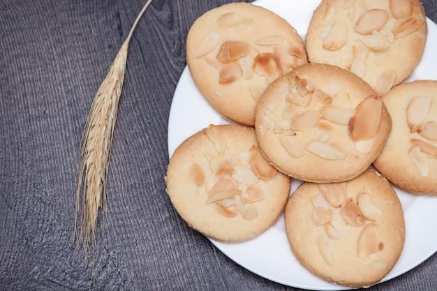 Geschmackvolle plätzchenkekse mit mandel und weizen auf der platte auf hölzernem hintergrund.