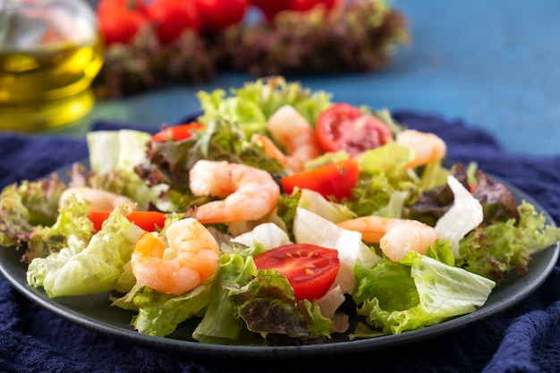 Geschmackvolle salatgarnelen, -tomaten und -mischgrüns auf einer platte. gesundes essen. diätessen. nahansicht