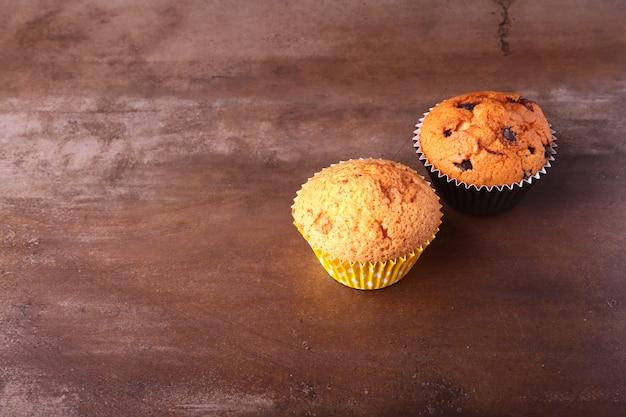 Geschmackvolle schokoladenkleine kuchen, muffins auf einem weißen holztisch