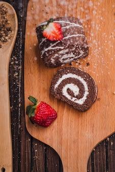 Geschmackvolle schokoladenrolle, die mit puderzucker besprüht