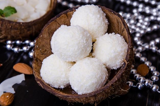 Geschmackvolle selbst gemachte kokosnusssüßigkeit mit mandeln und frischkäse auf hölzernem hintergrund