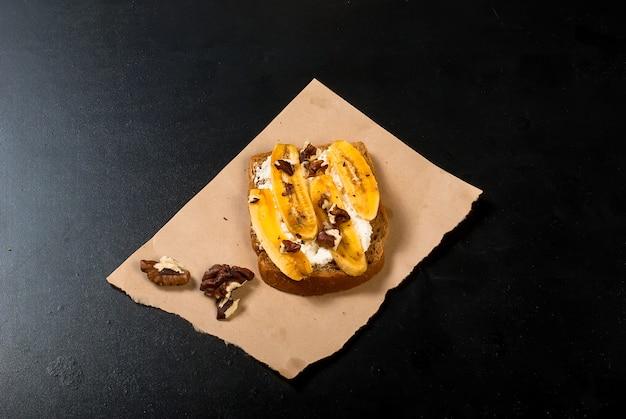 Geschmackvolle süße sandwiche mit bananen, nüssen und schokolade, auf schwarzer tabelle