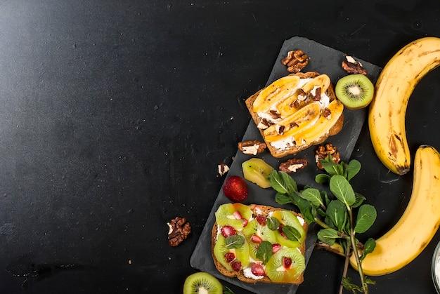 Geschmackvolle süße sandwiche mit bananen, nüssen und schokolade, kiwi, erdbeeren und minze auf schwarzem hintergrund