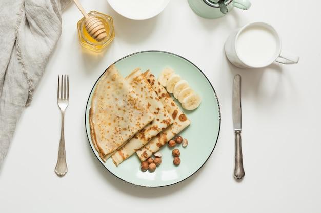 Geschmackvolle traditionelle russische frühstückspfannkuchen, milch, sauerrahm, honig. frühling. fastnacht.