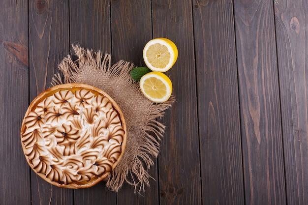 Geschmackvolle zitronentorte mit weißer creme diente auf holztisch