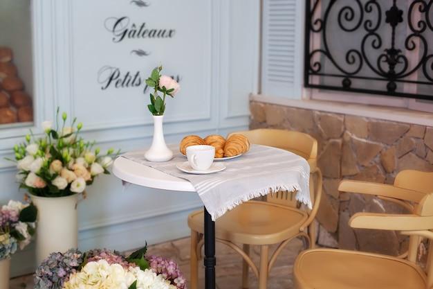 Geschmackvoller frühstückstasse kaffee mit hörnchen nähern sich bäckerei am morgen. kontinentales traditionelles frühstück. frühstück im straßencafé. guten morgen. morgenkaffee auf der terrasse. frühstück draußen. dekor