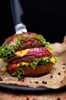 Geschmackvoller gegrillter doppelter burgercheeseburger mit pfeffer und salat