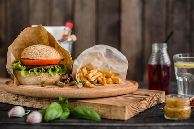 Geschmackvoller hamburger mit fleisch und gemüse gegen einen dunklen hintergrund. fast food. es kann als hintergrund verwendet werden