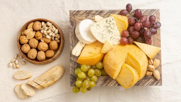 Geschmackvoller käse der draufsicht mit trauben und nüssen