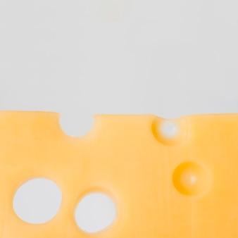 Geschmackvoller käse mit löchern auf weißem brett
