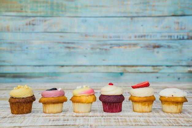 Geschmackvoller kleiner kuchen auf holztisch auf weinlesehintergrund