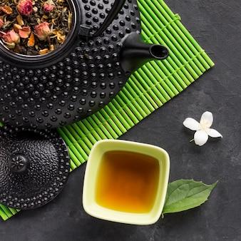 Geschmackvoller kräutertee und trockenes teekraut mit weißer jasminblume auf schwarzem hintergrund