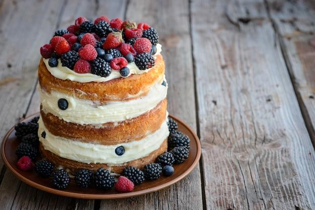 Geschmackvoller kuchen mit erdbeere, himbeere und brombeere auf einem holztisch