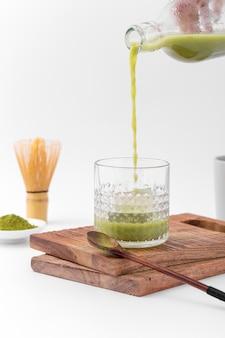 Geschmackvoller matchatee, der in ein glas gießt