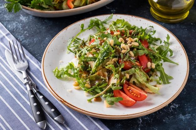 Geschmackvoller salat arugula, kirschtomaten und kiefernnüsse in einer platte. abnehmen