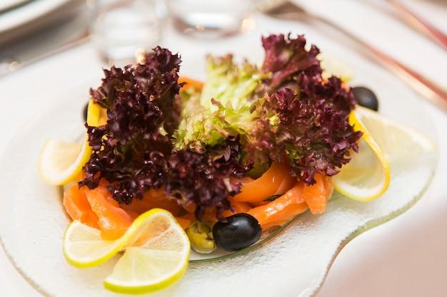 Geschmackvoller salat auf glasplatte auf festlicher tabelle im restaurant. salat, fisch, zitrone und oliven