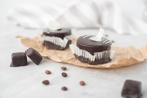 Geschmackvoller schokoladenkleiner kuchen und kaffeebohnen auf pergamentpapier