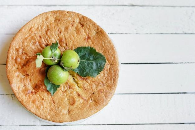 Geschmackvoller selbst gemachter apfelkuchen auf weißem hölzernem mit kopienraum
