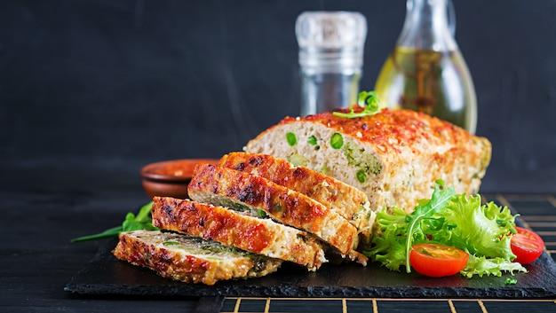 Geschmackvoller selbst gemachter boden backte hühnerhackbraten mit grünen erbsen und brokkoli auf schwarzer tabelle. amerikanisches fleischstück des lebensmittels.