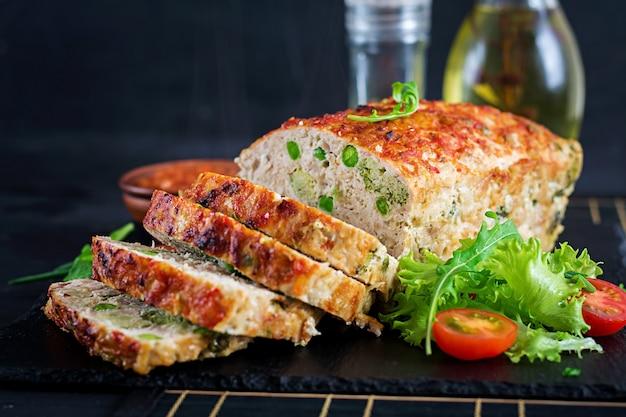 Geschmackvoller selbst gemachter boden backte hühnerhackbraten mit grünen erbsen und brokkoli auf schwarzer tabelle.
