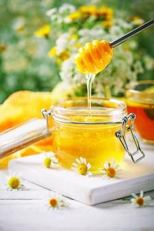 Geschmackvoller und gesunder honig auf weißem holztisch mit blumen der kamille.