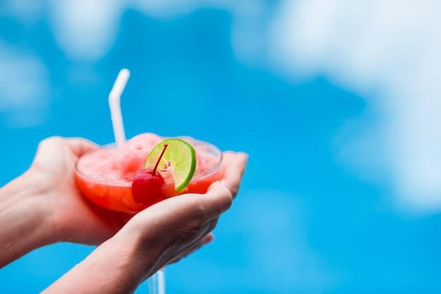 Geschmackvolles cocktail im frauhandtürkismeer