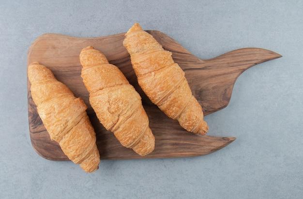 Geschmackvolles croissant an bord, auf dem marmorhintergrund. hochwertiges foto