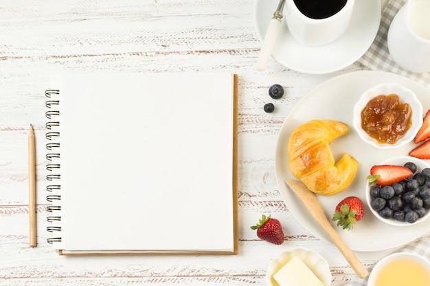 Geschmackvolles frühstück der draufsicht mit notizbuch