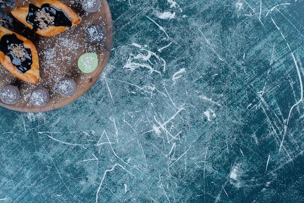 Geschmackvolles kuchencroissant und traube auf dem brett, auf dem blauen hintergrund. hochwertiges foto