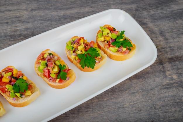 Geschmackvolles sandwich mit tomaten- und avocadogemüse auf hölzernem hintergrund