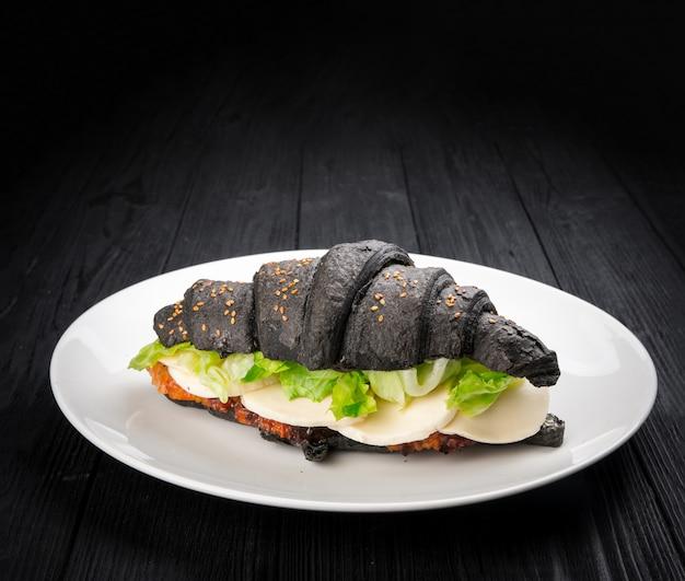 Geschmackvolles schwarzes hörnchen mit dem anfüllen auf rustikalem schwarzem hölzernem hintergrund