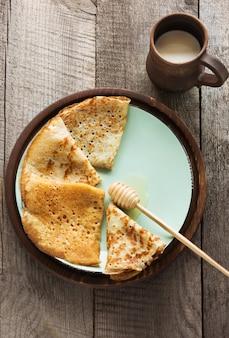 Geschmackvolles traditionelles russisches frühstück von pfannkuchen mit honig auf platte.