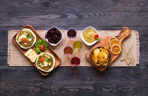 Geschmackvolles und köstliches bruschetta mit avocado, tomaten, käse, kräutern, chips und alkohol, auf einem hölzernen hintergrund.