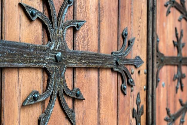 Geschmiedetes türmuster, dekorativ. alter weinleseeingang, enorme schwere holztür der kirche oder der kathedrale.