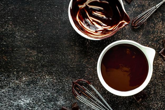 Geschmolzene dunkle schokolade in einer weißen kleinen schüssel