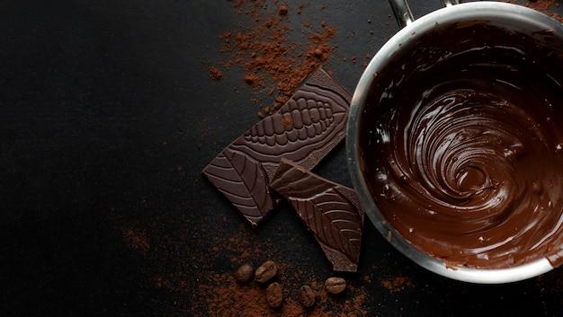Geschmolzene schokolade im topf mit schokoladenstücken auf dunkler oberfläche