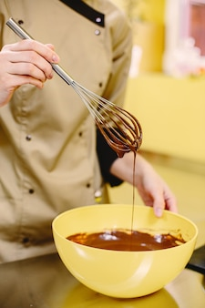 Geschmolzene schokolade. konditor mit schneebesen.