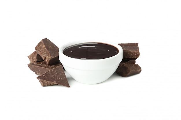 Geschmolzene schokolade und schokoladenstücke isoliert auf weiß