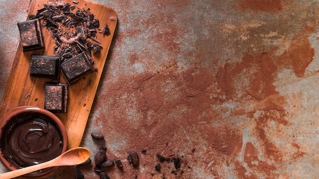 Geschmolzene schokoladenschüssel und zerquetschte stange auf hackendem brett mit hölzernem löffel