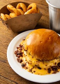 Geschmolzener käse und speck hamburger mit zwiebelringen über hölzernem hintergrund