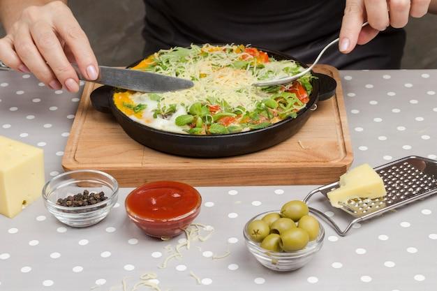 Geschmorte eier und gemüse in einer pfanne. hände halten eine gabel und ein messer. käse, reibe, oliven, paprika auf dem tisch
