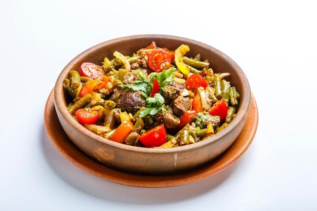 Geschmorte hühnerleber mit gemüse auf einer tonplatte. stücke leber, zwiebel, bohnen, tomate. lorbeerblatt. platte auf einem weißen hintergrund. georgische küche.