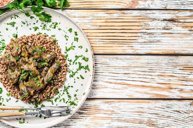 Geschmorte hühnermägen mit gemüse und buchweizen