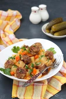 Geschmorte kartoffeln mit fleischbällchen auf einem weißen teller auf dunklem hintergrund, vertikale ausrichtung