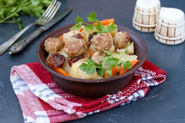 Geschmorte kartoffeln mit fleischbällchen, karotten und sonnengetrockneten tomaten in einer schüssel vor einem dunklen hintergrund