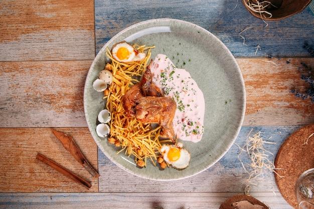 Geschmorte wachtel mit pai-kartoffeln, kichererbsen und eiern